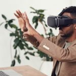 man using virtual reality device near laptop