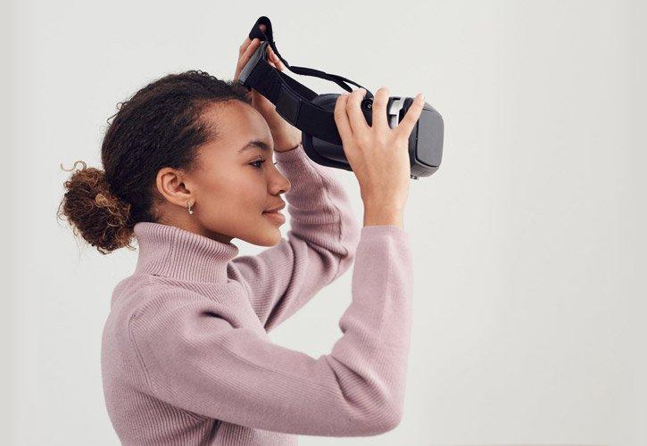 woman putting on virtual reality device